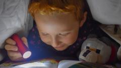 Child reading a book in the dark using a torch